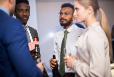 Multiethnic group of stylish office workers celebrating corporate event, chatting and drinking alcohol